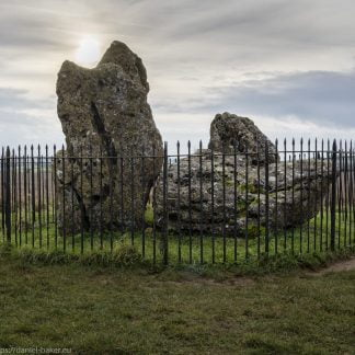 Neolithic stones surrounded by black iron fence with the winter solstice sun shining above