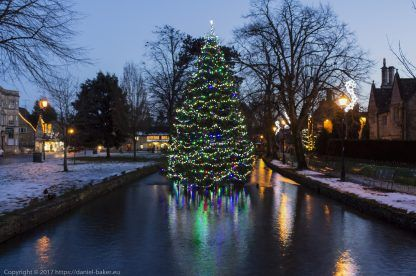 A beautifully decorated Christmas tree seemingly floating in the river at Bourton-on-the-water
